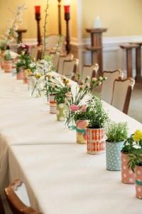 Des fleurs dans des pots recouverts de papiers colorés ou de tissus. Simple à réaliser avec des cannes de conserves de formats similaires.